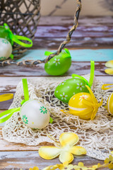 Easter eggs on wooden background colorful green yellow basket