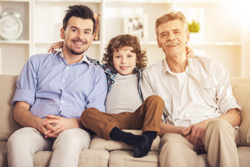 Generation portrait. Grandfather, father and son sitting on sofa