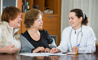 Young physician receiving mature patients in clinic