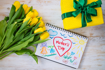 overhead view. mother day card with flowers and gift box on wooden background