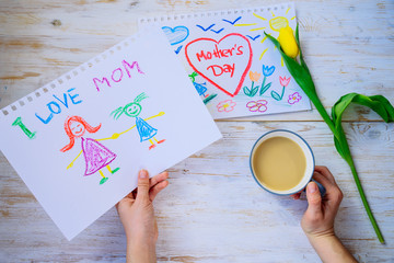 mother look on kid picture with mother day congratulation while drink coffee. overhead view