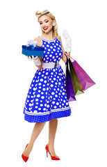 Full body portrait of woman in pin-up style blue dress in polka dot holding gift box and shopping bags, isolated on white background