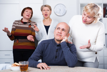 Mature male is sitting upset and woman is apologizing