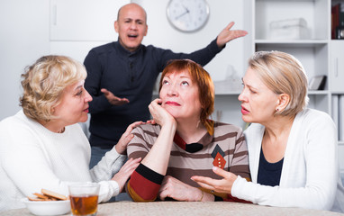 Mature woman is sitting upset and her girlfriends are expressioning understanding to she