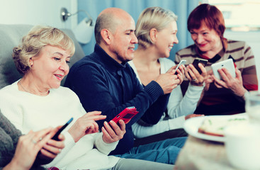 Mature friends are sitting on sofa and chatting on phone