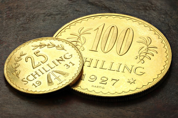 Austrian 25 and 100 Schilling gold coins on rustic wooden background