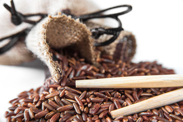 Wild red rice with sticks on white background