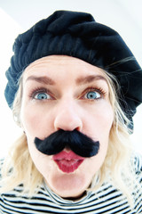 funny portrait of blond woman as french man with beret and mustache