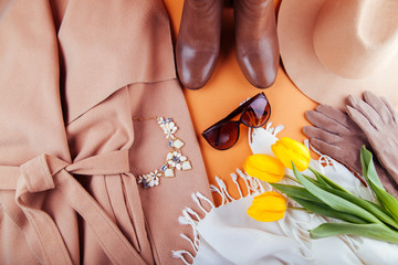 Spring female outfit with yellow tulips. Set of clothes, shoes and accessories on orange background