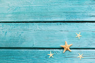 Summer sea background - starfish on blue wooden background