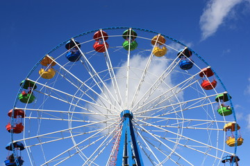 Colourful Ferris Wheel over the blue clear sky with red, green, blue and yellow cabins