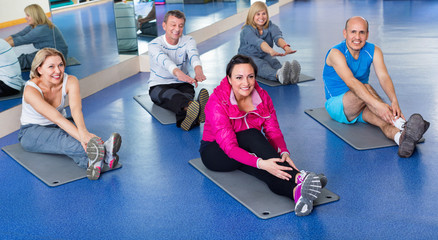 Group of mature people exercising on sport mats