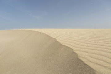 Sand dunes in the desert under a blue sky