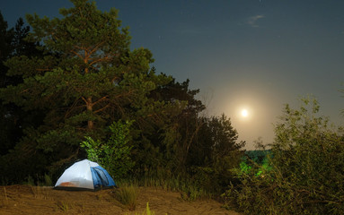 tourist tents on a sandy beach at night with moonlight surrounded by trees under a starry sky advertising background