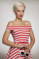 Vintage style portrait of young beautiful blond woman in striped dress