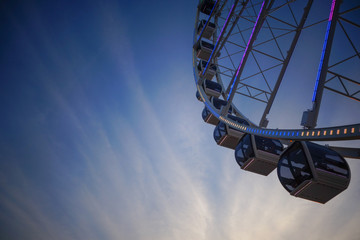 Modern Ferris wheel on evening sky background. Free text copy space.
