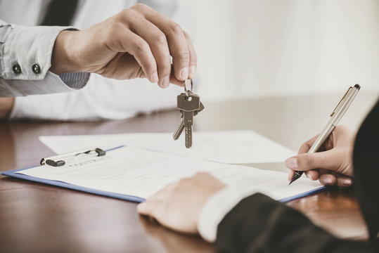 Young woman is signing financial contract with male realtor