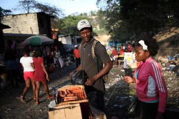 A man selling hot-dogs speaks to a customer in Port-au-Prince