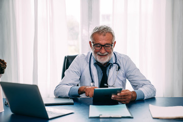 Senior doctor at desk looking at his tablet