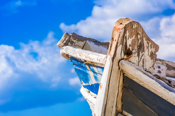 Detail of a wooden shipwreck with cloudy blue sky background.
