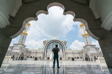 Young man traveler with backpack walking to Wilayah Persekutuan mosque in Kuala Lumpur, Malaysia..