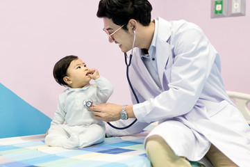 Asian doctor man examining a little boy by stethoscope in hospital. Medicine and health care concept..