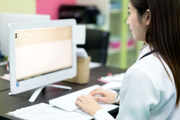 Asian woman doctor searching patient information from medical record system by using computer in hospital..