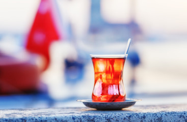 Turkey, Istanbul. Istanbul traveling welcome concept. Traditional Turkish glass of tea on parapet at Maiden tower background. Sunset time scene.