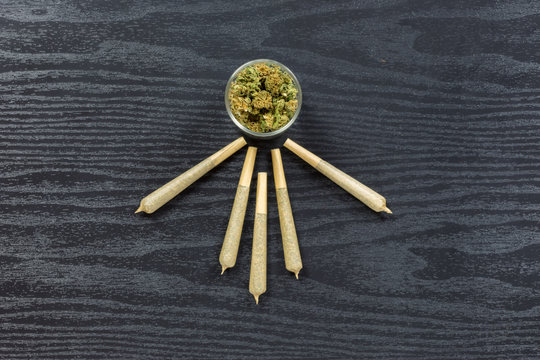 Weed in glass jar with joints arranged on black textured surface