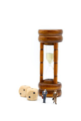 Miniature people :  businessman look a watch  stand with Sandglass, hourglass.