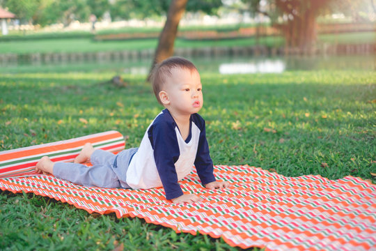 Cute little Asian 18 months / 1 year old toddler baby boy child concentration on practices yoga in Cobra Pose and meditating outdoors on nature in summer time, Healthy lifestyle, Yoga for Kids concept