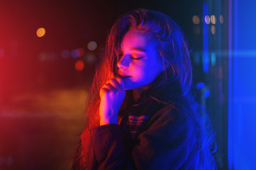 Sexy young woman posing over night city dramatic neon background