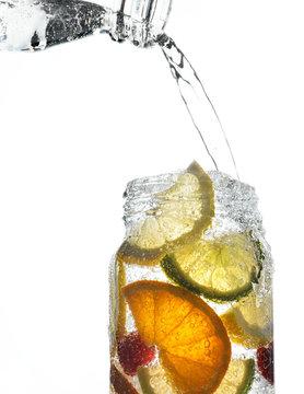 Sparkling water pouring over jar of translucent fruit slices