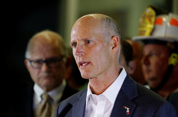 Florida Governor Rick Scott speaks to the media as rescue efforts continue after a pedestrian bridge collapsed at Florida International University in Miami
