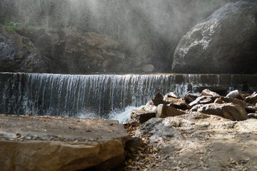 Low waterfall with water fog and indistinct pedestrian trail on the background