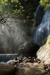 Waterfall and lower cascade in the forest with water fog lit with sunbeams