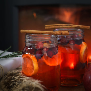 Holiday mulled fruit punch by the fire with cinnamon garnishes