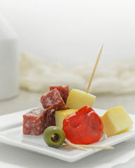 Salami and cheese appetizer with pepper and olive garnish on white plate