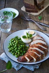 Baked chicken breast, egg and green peas on a plate