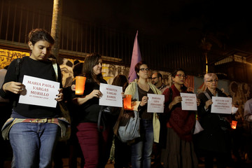People hold signs with the names of victims of femicide during a protest and vigil against femicide in San Jose