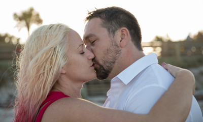 couple closes eyes to kiss passionately at sunset