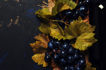 Red wine in bottle and grapes, black background, top view Fototapete