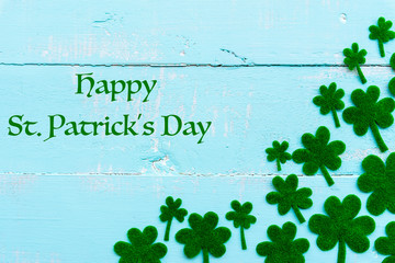 Happy St Patricks Day message and a lot of green paper clover leaf on Pastel white and blue wooden table background texture.