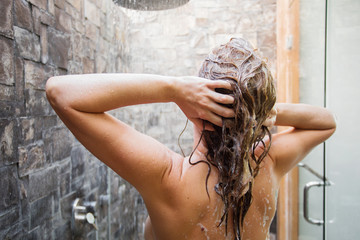 Woman washing head in shower