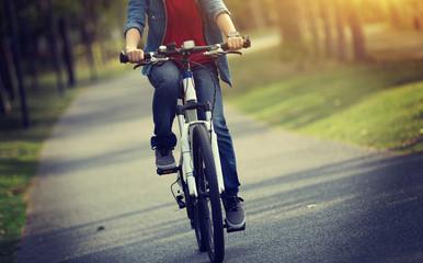 woman cyclist riding bike in tropical park