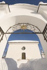 gate towards a church in a winter landscape
