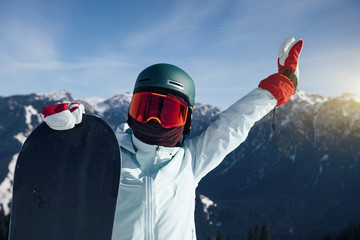 happy snowboarder with snowboard on winter mountain top
