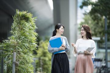 会話をしながらオフィス街を歩く女性社員達