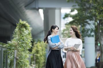 資料とタブレットを持って外を歩く女性たち