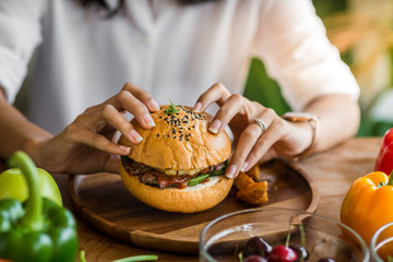 Woman holding meat burger in restaurant.